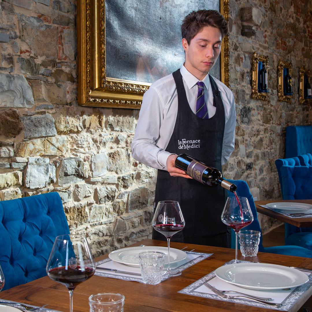 Pranzo a La Fornace de' Medici. Il nostro personale sempre disponibile per le vostre esigenze. L'interno del nostro ristorante, pietra a vista e cornici d'orate aiutano la luce del sole a creare atmosfere intense. Lorenzo, il nostro cameriere versa al vino a dei clienti pronti ad assaporare nuove esperienze.