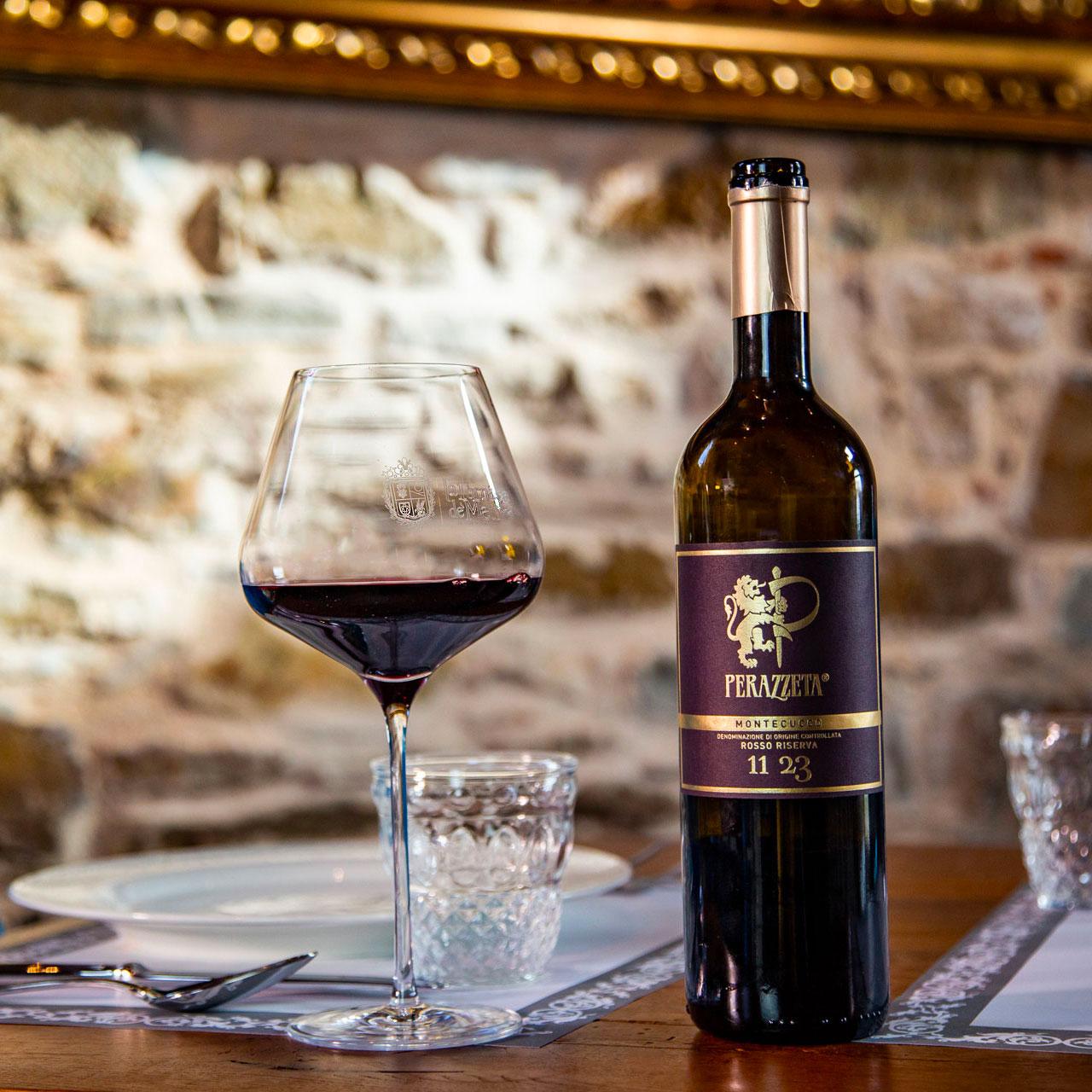 Una bottiglia di vino rosso sul tavolo de La Fornace de' Medici alle porte del Mugello perazzeta. Vino rosso, atmosfera gioiosa e piena di relax. Siamo qua per donare gioia e serenità.