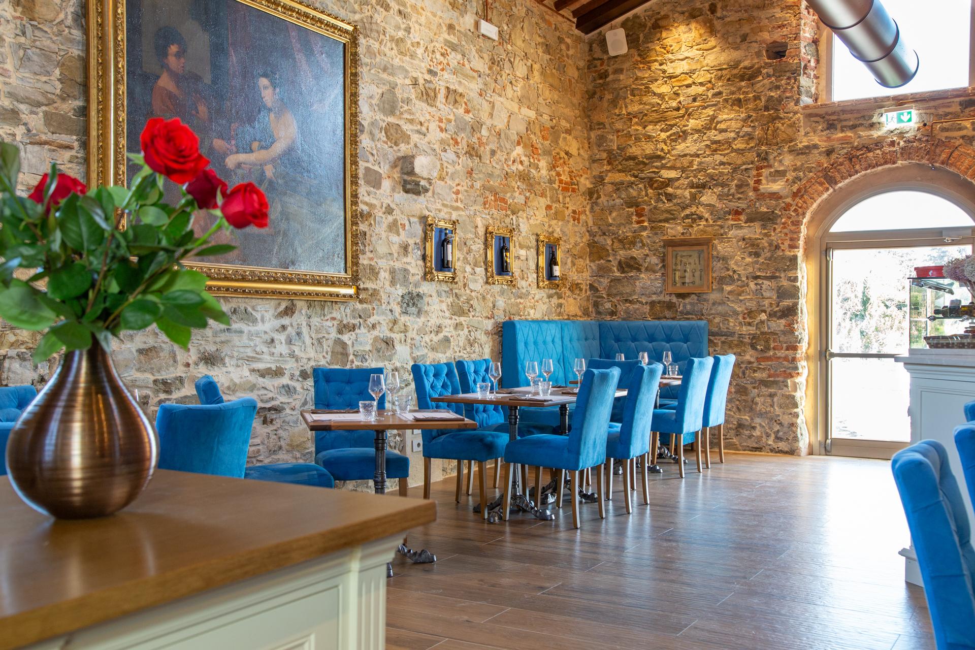 Sala da Pranzo La Fornace de Medici. Un luogo pieno di storia e di arte, i fiori di stagione accompagnano con forti contrasti il colore blu acceso delle sedie in veluto.